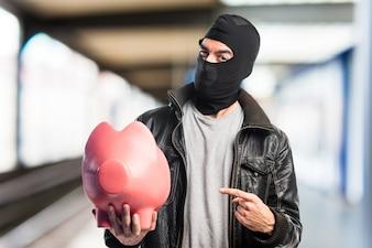 Robber holding a piggybank