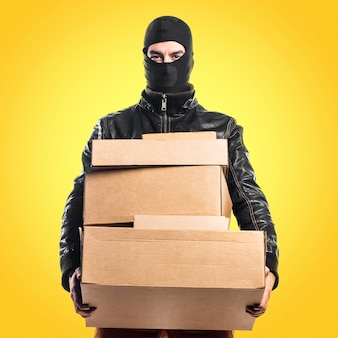 Robber holding boxes on colorful background