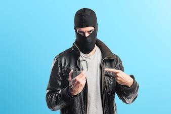 Robber holding vintage padlock on colorful background
