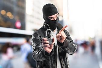 Robber holding vintage padlock on unfocused background