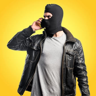 Robber talking to mobile on colorful background