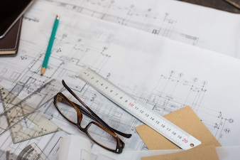 Rolls of architectural house plans with compass, pencil, ruler and glasses