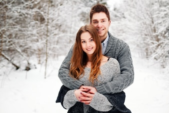 Romantic couple hugging in snow