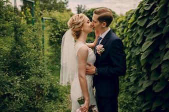 Romantic newlyweds kissing outdoors