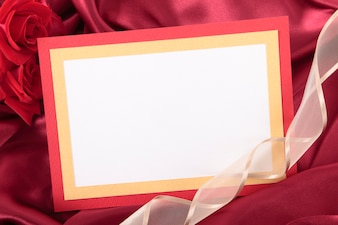 Romantic valentine card with ribbon on red silk