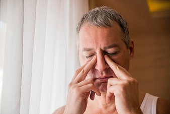 Sad and depressed man holding his head with his hand, standing by the window. man holds his nose and sinus area with fingers in obvious pain from a head ache in the front forehead area