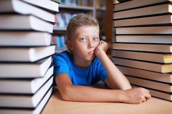 Sad kid surrounded by books