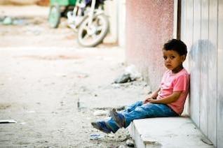 sad little boy waiting outside