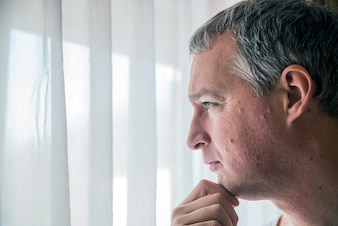 Грустный мужчина смотрит в окно. Чувство безнадежности. Подавленный зрелый человек, стоящий около окна. Человек, страдающий депрессией