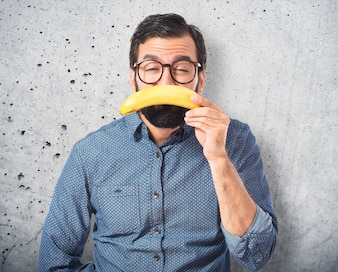 Sad young hipster man with banana
