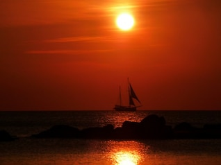 Sail ship at sunset in red