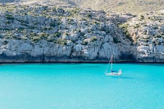 Sailboat sailing on transparent sea