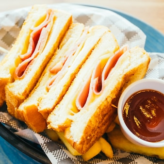 Sandwich with ham cheese and french fries and tomato sauce