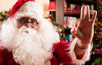 Santa claus doing an okay gesture in home