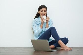 Satisfied Woman Drinking Tea on Floor with Laptop