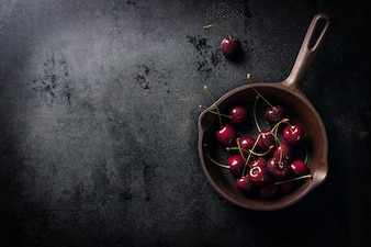 Saucepan with cherries on a black wooden table seen from above