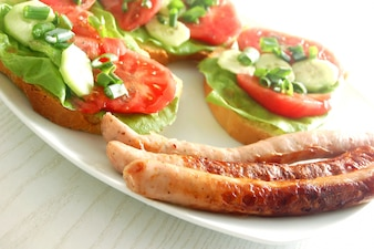 Sausages with avocado and tomato
