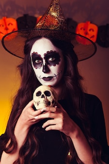 Scary witch holding skull