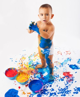 Schoolboy playing with pots full of paint