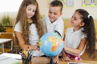 Schoolchildren studying globe standing in classroom