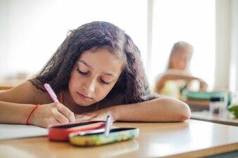 Schoolgirl sitting at desk writing