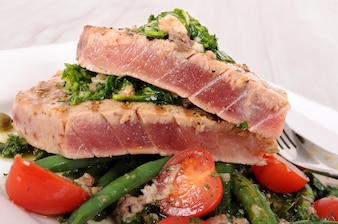 Seared tuna steak with vegetables close up