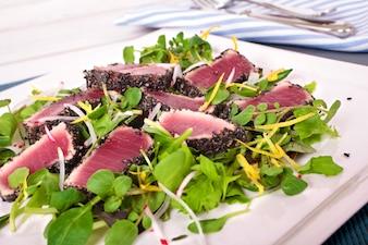Seared tuna with green salad on table