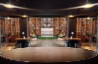 選択されたフォーカス空の茶色の木製テーブルとコーヒーショップやレストランボケの画像を背景にぼかし。あなたのフォトモンタージュまたは製品のディスプレイ用です。