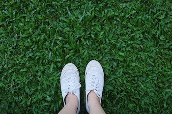 コピースペース、春と夏のコンセプトと緑の草の背景にスニーカー靴の足のSelfie