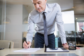 Senior Businessman Bending over Desk and Writing