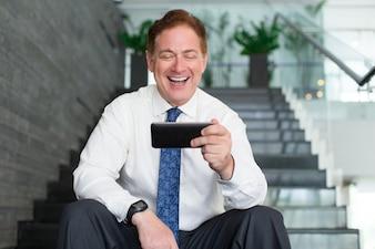 Senior businessman laughing at internet video