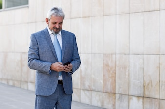 Senior businessman texting with smartphone outside of modern office building.