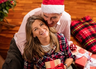 Senior couple with gifts sitting on the floor