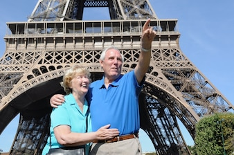 Senior man pointing at something to his wife next to the eiffel tower