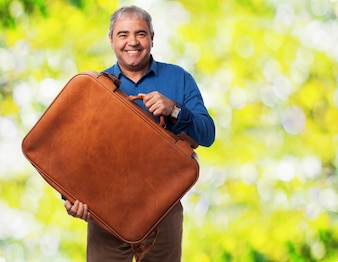 Senior man smiling with a travel suitcase