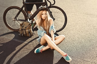Sensual woman sitting on the floor with bike background