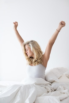 Serene young woman sitting on bed and stretching