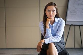 Serious Adult Businesswoman Sitting near Flipchart