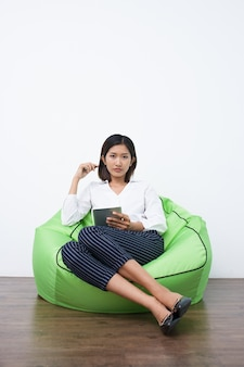 Serious Asian businesswoman with sitting on beanbag