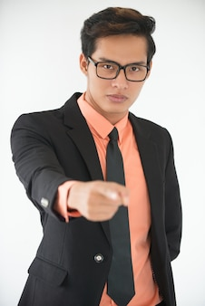 Serious businessman in glasses pointing at you
