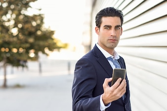 serious businessman with a mobile in hand