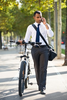Serious Businessman with Bike Talking on Phone