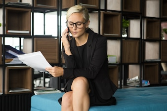 Serious businesswoman talking on phone to partner