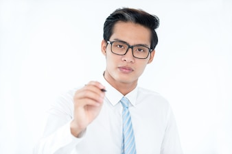 Serious calm Asian businessman drawing on invisible board