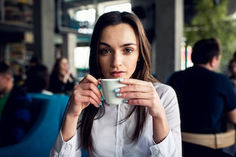 Serious girl having coffee in a bar