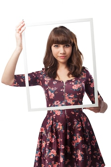 Serious girl holding a frame in front of her