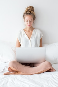 Serious Girl Working on Laptop and Sitting on Bed