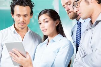 Серьезная леди, показывающая планшетный компьютер для коллег