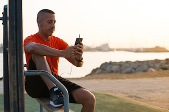 Serious male athlete listening to music from phone