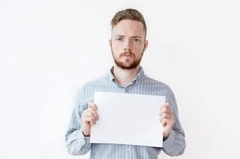 Серьезный человек, держащий пустой лист бумаги